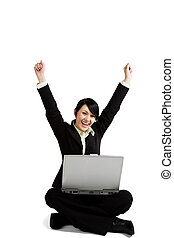 A happy and successfull businesswoman with her arms raised working with a laptop