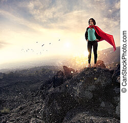 Successful businesswoman acts like a super hero on a mountain. Concept of determination and success