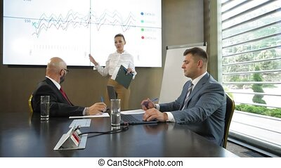 Successful businesswoman giving presentation to business team in slow motion