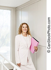 Successful businesswoman standing in hallway