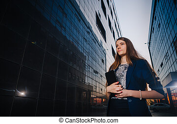 Successful businesswoman  stands on the background of buildings and holding tablet computer. City business woman working.