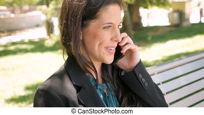 Successful businesswoman talking on mobile phone on park...