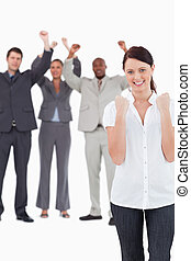 Successful businesswoman with cheering colleagues behind her