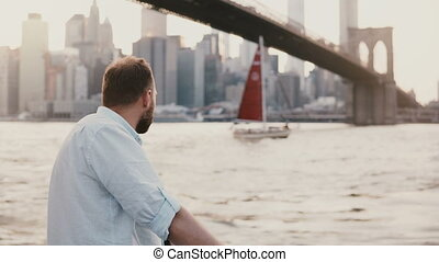 Successful Caucasian freelance businessman stands at river embankment under Brooklyn Bridge New York, red boat passes by