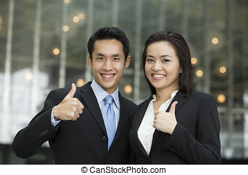Successful Chinese business team with thumbs up.