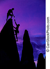 Team of climbers conquer the summit of a challenging rock spire.