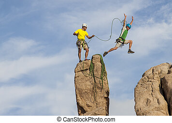 Team of male climbers conquer the summit of a challenging rock spire.