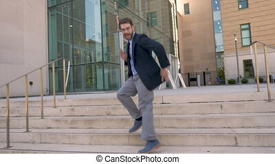 Successful corporate man doing crazy dance down steps...