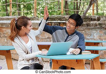 Successful couple using laptop and giving high five outdoors...