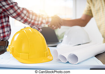 Successful deal and cooperation concept, Architect and engineer construction workers shaking hands while working with building contractor in office