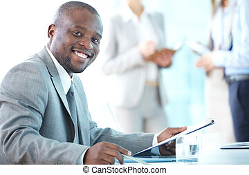 Close-up shot of a smiling entrepreneur working in office