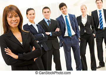 Portrait of successful businesswoman looking at camera with smile on background of elegant employees