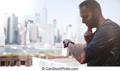 Successful European businessman smiling, using smart watch to communicate at epic Manhattan skyline, New York City.