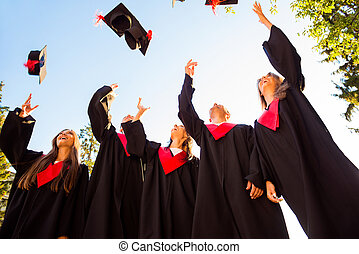 Successful five students with congratulations together throwing graduation hats in the air and celebrating