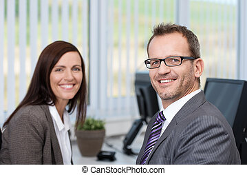 Successful friendly businessman wearing glasses sitting in...
