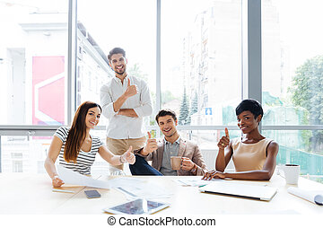 Successful group of business people showing thumbs up in office