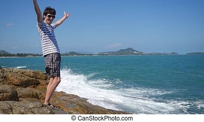 Successful happy businessman raising hands to the sky by the sea with splashing waves on the rock in slow motion.