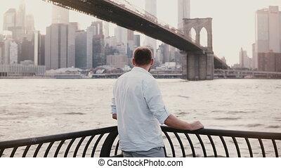 Successful happy businessman stands near Brooklyn Bridge...