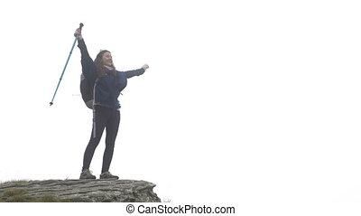 Successful happy climber girl in expedition celebrating the achievement of reaching misty mountain top raising hands