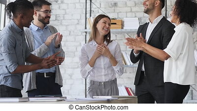 Successful happy shy best female worker leader get team applause in office, multiracial employees group clapping hands congratulate cheerful proud businesswoman with professional achievement concept