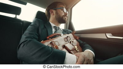 Successful lawyer in suit riding in luxury car with bag - ...