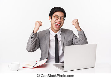 Successful lucky young asian office manager, triumphing as got great deal, sitting at table with wireless earphones, clench fists and pump hands up in victory, celebrating, use laptop