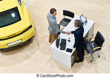 Successful Man Buying Car in Showroom