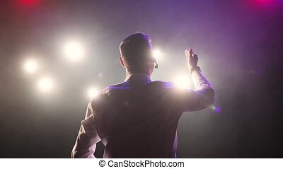 Successful man comedian speaks jokes in micropphone stands on stage, back view.