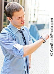 Successful man looking at his watch. Over urban background.