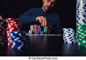 Successful man poker player counting his chips seated at the casino table. Gambling tournament winner