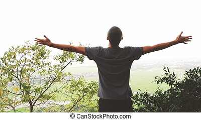 Successful man raising arms after cross track running on...