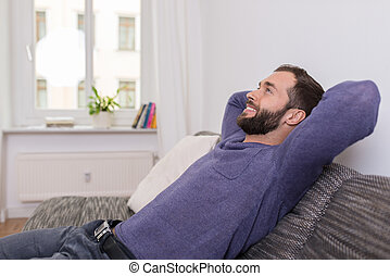 Successful man relaxing on the sofa at home sitting with his...