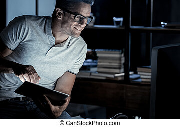 Successful mature guy working on laptop later at night