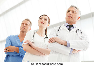 Successful medical team. Successful doctors team standing together with their arms crossed