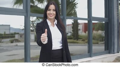 Successful motivated young businesswoman giving a thumbs up...