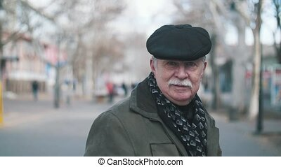 Successful old man with white mustache standing in a street...