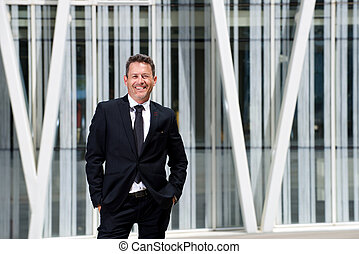 Successful older businessman standing by modern architecture