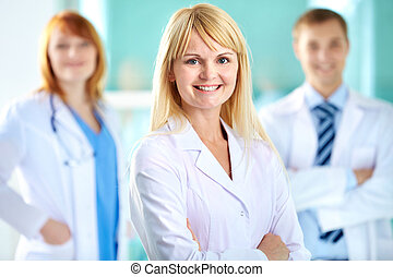 Portrait of pretty clinician in white coat looking at camera with smile