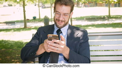 Successful salesman sitting on park bench using smart phone...