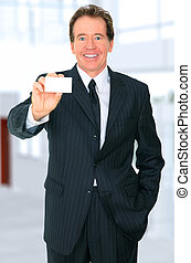 Successful Senior Businessman Showing Business Card
