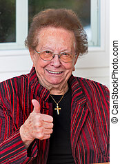 Successful senior citizen laughs with thumbs up - Old woman...
