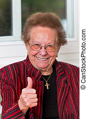 Successful senior citizen laughs with thumbs up