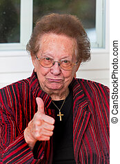 Successful senior laughs with thumb up - Old woman...