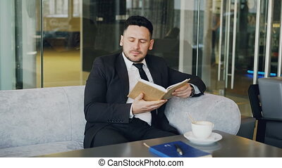 Smart Caucasian businessman in formal clothes reading text...