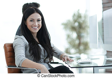 Successful smiling business woman sitting at the desk