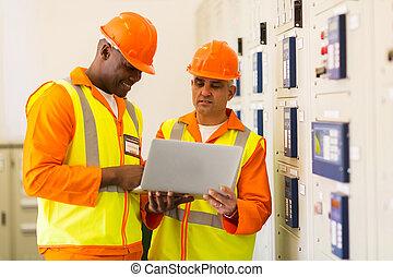 technicians using laptop in control room