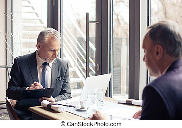 Successful two businessmen are negotiating in restaurant