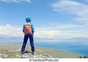 successful woman backpacker enjoy the view on mountain peak
