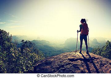 successful woman hiker at sunrise mountain peak