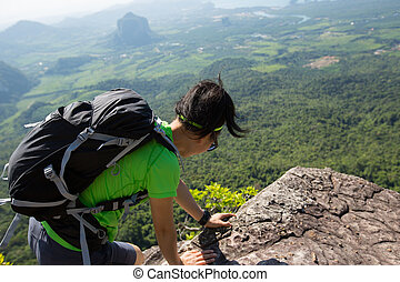 successful woman hiker climbing rock on mountain peak cliff